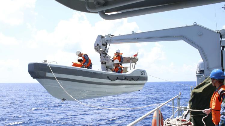 A search boat carrying rescue workers is set down from Mianyang warship on the waters suspected to be the site of the missing Beijing-bound Malaysia Airlines flight MH370
