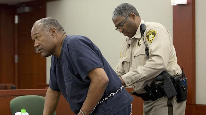 O.J. Simpson, left, has one hand freed from his handcuffs as he returns to the witness stand to testify after a break during an evidentiary hearing in Clark County District Court, Wednesday, May 15, 2013 in Las Vegas. Simpson, who is currently serving a nine to 33-year sentence in state prison as a result of his October 2008 conviction for armed robbery and kidnapping charges, is using a writ of habeas corpus, to seek a new trial, claiming he had such bad representation that his conviction should be reversed. (AP Photo/Julie Jacobson, Pool)