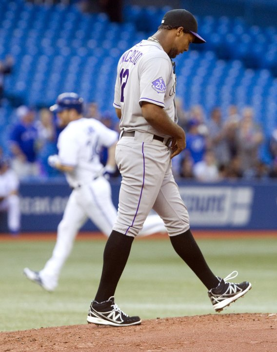 Colorado Rockies Juan Nicasio walks off the mound after giving up a three-run home run to Toronto Blue Jays Adam Lind, who is rounding the bases behind him, in their interleague MLB game in Toronto