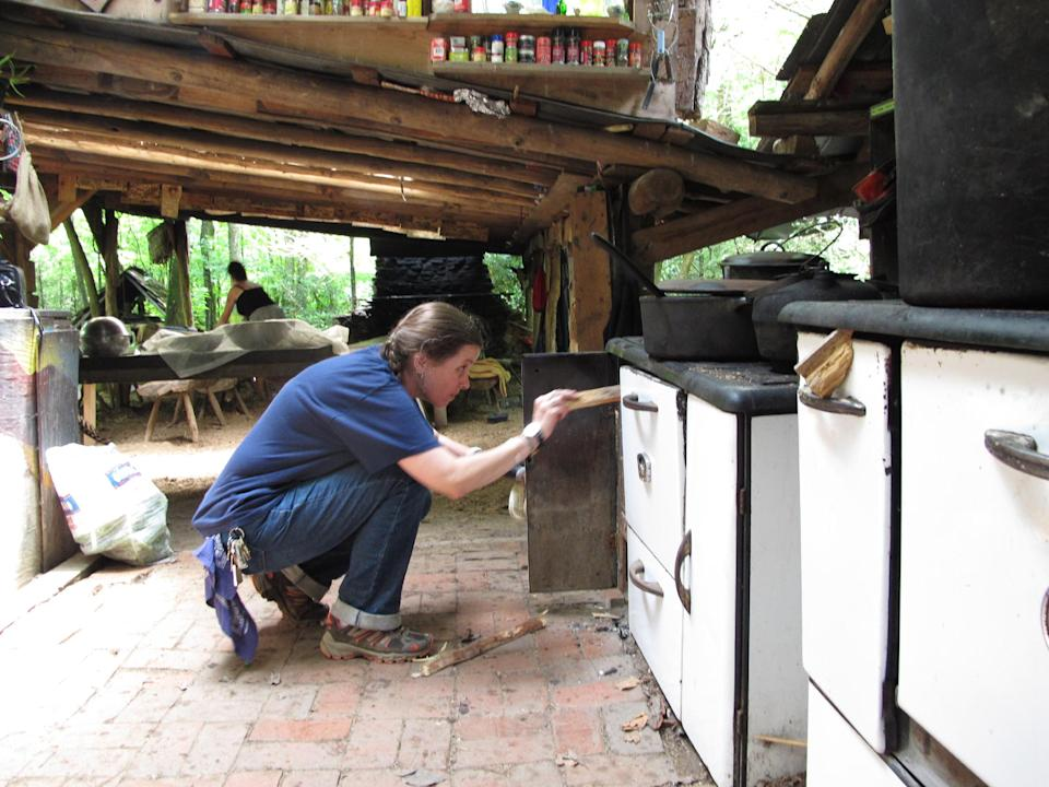 Volunteer Thai Williams stokes the fire in a wood stove at Turtle Island Preserve in North Carolina on Thursday, June 27, 2013. People like the special education teacher from Charlotte come from all over the world to learn natural living and how to go off-grid, but local officials ordered the place closed over health and safety concerns.AP Photo/Allen Breed)