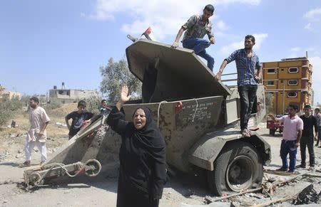 A Palestinian woman gestures in front of an Israeli military equipment, which witnesses said left behind by Israeli forces during a ground offensive, east of Khan Younis in the southern Gaza Strip