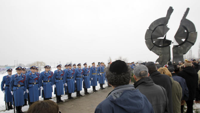 Serbian military honor guards stand to attention as people attend commemorations for victims of the Holocaust at a monument erected in the former World War II Nazi concentration camp of Sajmiste in Belgrade, Serbia, Sunday, Jan. 27, 2013. The ceremony coincided with International Holocaust Remembrance Day, which marks the liberation of the Auschwitz Nazi concentration camp on Jan. 27, 1945. (AP Photo/Darko Vojinovic)