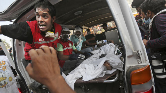 A Bangladeshi garment worker who was pulled alive from the rubble lays in the back of an ambulance after being brought by rescue workers at the site of a building that collapsed Wednesday in Savar, near Dhaka, Bangladesh, Friday, April 26, 2013. The death toll reached hundreds of people as rescuers continued to search for injured and missing, after a huge section of an eight-story building that housed several garment factories splintered into a pile of concrete. (AP Photo/Kevin Frayer)
