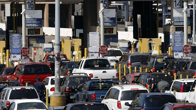 FILE - This Sept. 22, 2009 file shows federal agents mixing into a swarm of automobiles as they do security checks  on vehicles waiting to enter the U.S. at the San Ysidro Border Crossing in San Diego. Federal agents at the border must be allowed to act on no more than a hunch when deciding whether to search a person's laptop, cell phone or other electronic device because any higher standard would prevent detection of terrorists and child pornographers and expose the government to damaging lawsuits, according to a censored version of an internal study conducted by the Department of Homeland Security. (AP Photo/Lenny Ignelzi, File)
