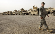 A U.S. army soldier walks past military Humvees which are ready to be shipped out of Iraq at a staging yard at Camp Sather, part of the sprawling U.S. military Victory Base Complex that is set to close in Baghdad, Iraq, Saturday, Oct. 15, 2011. The U.S. has promised to withdraw from Iraq by the end of the year as required by a 2008 security agreement between Washington and Baghdad. Some 41,000 U.S. troops are scheduled to clear out along with their equipment. It's still unclear if the U.S. military will keep several thousand troops in Iraq as leaders weigh whether staunch political opposition in both nations is worth the risk. The uncertainty has been a logistical nightmare for American commanders, who could be asked at the last minute to keep some equipment and manpower back but for now must push ahead in case the withdrawal plan stands. (AP Photo/Khalid Mohammed)