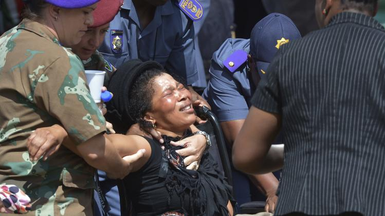 A woman is carried away after paying her respects to former South African President Mandela in Pretoria