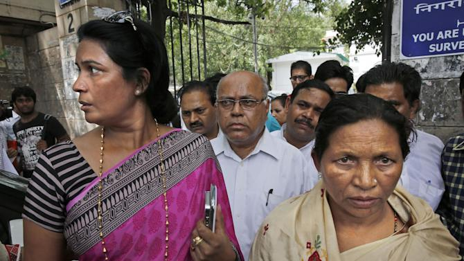 """Rukmani Devi, sister of India's famous """"Bandit Queen"""" Pholan Devi, right, and Shikha Singh, a relative of Phoolan's killer Sher Singh Rana, walk out of a court after judgment was passed in the murder case, in New Delhi, India, Thursday, Aug. 14, 2014. The upper-caste killer of Devi was sentenced Thursday to life in prison by a court for gunning down the outlaw-turned-legislator who was idolized as a champion of the lower castes. (AP Photo /Manish Swarup)"""