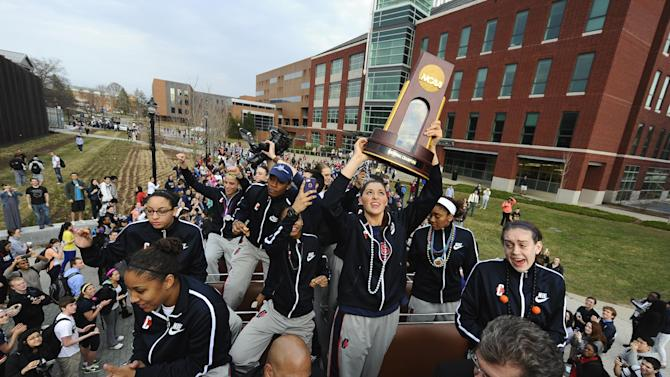 Connecticut's Stefanie Dolson holds the championship trophy as she rides with the team on a double-decker bus during a parade through campus honoring the team's win in the NCAA women's college basketball tournament, in Storrs, Conn., Wednesday, April 10, 2013. (AP Photo/Jessica Hill)