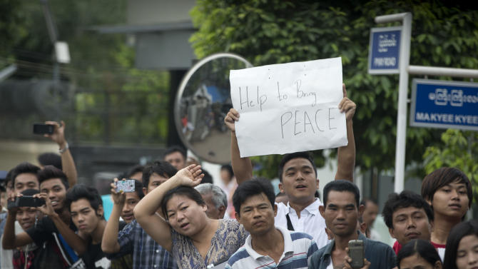 """A man holds a sign reading: """"Help to bring peace"""" as people line the street to see U.S. President Barack Obama traveling in his motorcade to meet with Myanmar's President Thein Sein at Yangon Parliament Building in Yangon, Myanmar, Monday, Nov. 19, 2012. This is the first visit to Myanmar by a sitting U.S. president. (AP Photo/Carolyn Kaster)"""