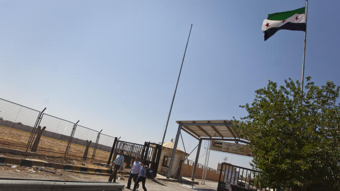 Three men cross from Turkey into Syria through the Bab Al-Salam border crossing, under control of the Free Syrian Army, near the town of Azaz , north of Aleppo, Syria,  Monday, Aug. 13, 2012. (AP Photo/ Khalil Hamra)