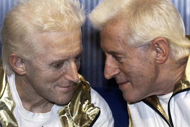 FILE - In this Dec. 17, 1986 file photo, Jimmy Savile, right, poses for photographers with a wax work model at Madame Tussauds museum in London. The BBC faced growing fallout Monday, Oct. 22, 2012 over sexual abuse allegations against Savile, as British Prime Minister David Cameron accused the broadcaster of changing its story about why it killed a news segment on the accusations. (AP Photo/John Redman, File)