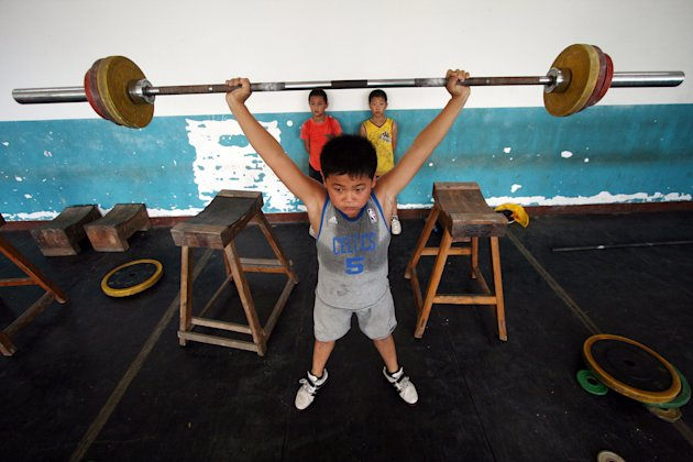 A Chinese boy practises weightlifting at a weightlifting training school in Jinjiang, in south China's Fujian province on July 22, 2011. Young Chinese athletes often enroll in sports schools in th