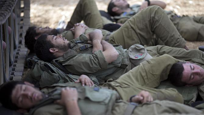 Israeli soldiers sleep in the shade of a military vehicle near the Israel Gaza Border, early Tuesday, July 15, 2014. The Israeli Cabinet has accepted an Egyptian proposal for a cease-fire to end a week of conflict with Hamas militants in the Gaza Strip that has killed 185 Palestinians and exposed millions of Israelis to Hamas rocket fire. No Israelis have been killed as a result of Hamas rocket launches. A senior Hamas official says the Palestinian militant group rejects an Egyptian proposal for a cease-fire with Israel. (AP Photo/Ariel Schalit)