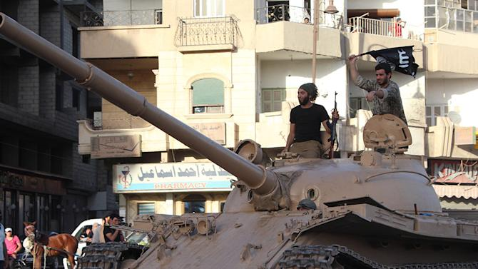 An image made available by Jihadist media outlet Welayat Raqa on June 30, 2014, allegedly shows a member of the IS (Islamic state) militant group parading with a tank in a street in the northern rebel-held Syrian city of Raqa