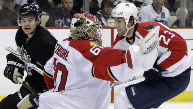 Pittsburgh Penguins' Chris Kunitz, left rear, beats Florida Panthers defenseman Tyson Strachan (23) and watches his shot sail over the glove hand of Florida Panthers goalie Jose Theodore (60) in the second period of an NHL hockey game in Pittsburgh on Friday, March 9, 2012. Panthers defenseman Theodore made the save on the shot. (AP Photo/Gene J. Puskar)