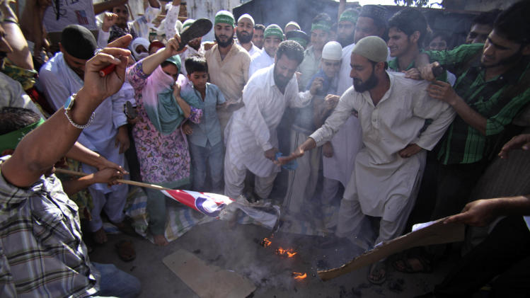 "Indian Muslims burn the U.S. flag and shout slogans against the United States during a protest rally against an anti-Islam film called ""Innocence of Muslims"" that ridicules Islam's Prophet Muhammad in Jammu, India, Friday, Sept. 21, 2012. (AP Photo/Channi Anand)"