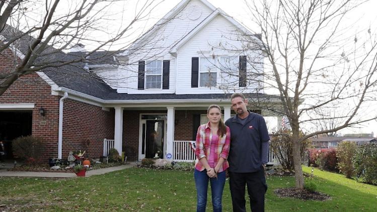 Barry Chipman, right, poses for a portrait with his daughter Billie, 16, in front of their home in Indianapolis Thursday, Nov. 15, 2012. The Chipman's home in the neighborhood where an explosion late Saturday evening killed two people, destroyed two homes and made dozens more uninhabitable. Damage to the home was limited to some drywall cracks and a dented garage door. (AP Photo/AJ Mast)