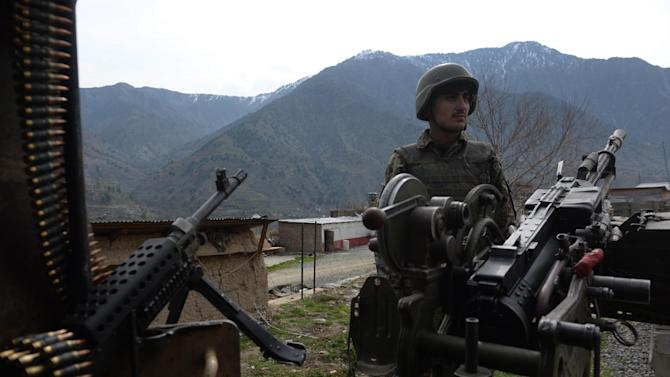An Afghan soldier stands guard in February 2014 near the army outpost in Kunar province near the Pakistan border, where security forces have launched an operation against militants