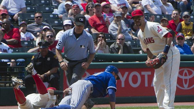 Toronto Blue Jays' Kevin Pillar slides safely back to third base as Cleveland Indians' first baseman Carlos Santana tries to tag him and Indians' third baseman Lonnie Chisenhall, right, watches along with umpire James Hoye  during the fourth inning of a baseball game, in Cleveland, Sunday, May 3, 2015. The Indians won the game 10-7. (AP Photo/Phil Long)