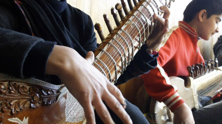 In this Monday,  Jan. 7, 2013, photo, an Afghan girl, Gulalai, left, practices playing the sitar in a class at the Afghanistan National Institute of Music in Kabul, Afghanistan. Dozens of Afghan teenagers including former street kids or orphans aged 10 to 22, will be playing in the Afghan Youth Orchestra which begins a 12-day U.S. tour on Feb. 3 and includes concerts at Washington's Kennedy Center - President Barrack Obama has been invited - New York's Carnegie Hall and the New England Conservatory in Boston. (AP Photo/Musadeq Sadeq)