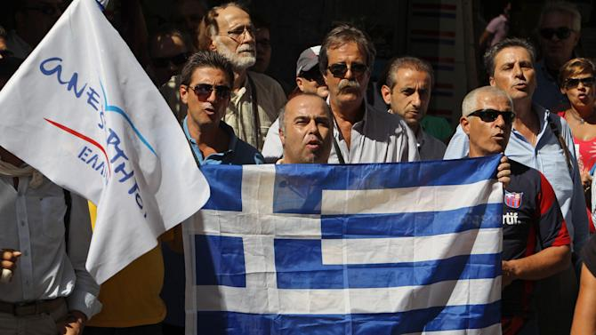 Supporters of the small right-wing Independent Greeks party, gathered outside the finance ministry before a meeting between Greece's finance minister and debt inspection teams from the International Monetary Fund, European Central Bank and European Commission, known as the troika, in Athens, Monday, Oct. 1, 2012. Greece's finance minister Yannis Stournaras will submit the 2013 draft budget to Parliament on Monday, as the government resumed negotiations with international creditors over a two-year additional austerity package. (AP Photo/Thanassis Stavrakis)