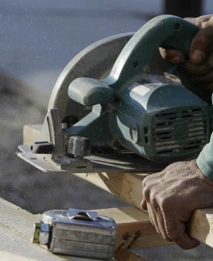 A carpenter uses a skill saw to cut a board as he works on building a new home Tuesday, Nov. 30, 2010 in Houston. Construction spending rose in October for the second straight month as residential building gains.(AP Photo/Pat Sullivan)