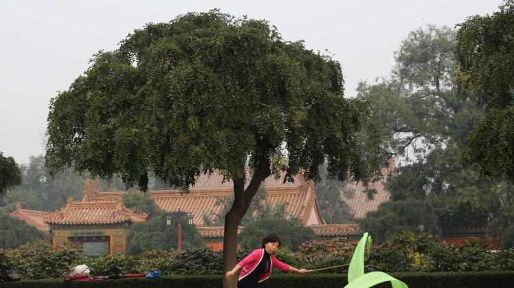 A woman exercises with a ribbon during a morning exercise session at Jingshan Park in Beijing