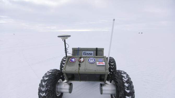"""In this July 15, 2011 photo, the """"Yeti,"""" a tractor-like autonomous robot, is tested for eventual deployment of ground-penetrating radar, at Summit Station, a remote research center operated by the U.S. National Science Foundation (NSF), and situated 10,500 feet above sea level, on top of the Greenland ice sheet. Across Greenland's vast white landscape, teams of researchers are searching for clues to the potential effects of global warming on Greenland's ice. (AP Photo/Brennan Linsley)"""