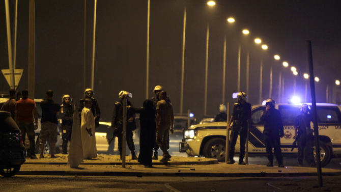 """Riot police keep villagers back from the site where a Bahraini youth was killed during an anti-government protest, allegedly by police shotgun fire, in the western village of Sadad, Bahrain, early Saturday, Sept. 29, 2012. An Interior Ministry statement said a police patrol was attacked with petrol bombs and iron rods, and one person died when """"policemen defended themselves."""" A witness among protesters said demonstrators were marching against the government when a policeman suddenly stepped out near the youth and shot him at close range. (AP Photo/Hasan Jamali)"""