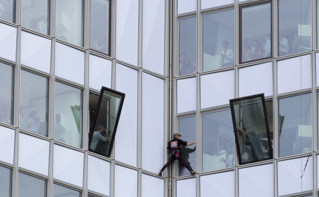 People look out of their windows as French urban climber Alain Robert, known as &amp;#39;Spiderman&amp;#39;, climbs up the 231 meter high (758 feet) First Tower, the tallest skyscraper in France, in the La De