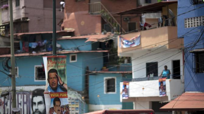 Posters featuring Venezuela's late President Hugo Chavez and interim President Nicolas Maduro hang on a pole at the 23 de Enero neighborhood in Caracas, Venezuela, Friday, April 12, 2013.  Maduro,who served as Chavez's foreign minister and vice president, is running against opposition candidate Henrique Capriles in Sunday's presidential election. AP Photo/Ariana Cubillos)