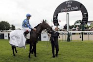 French jockey Antoine Hamelin (L), riding Saonois, celebrates with groom Eric Vandra (C), during the French Derby (Prix du Jockey Club) at Chantilly, northern of Paris. Hamelin won the Prix du Jockey-Club