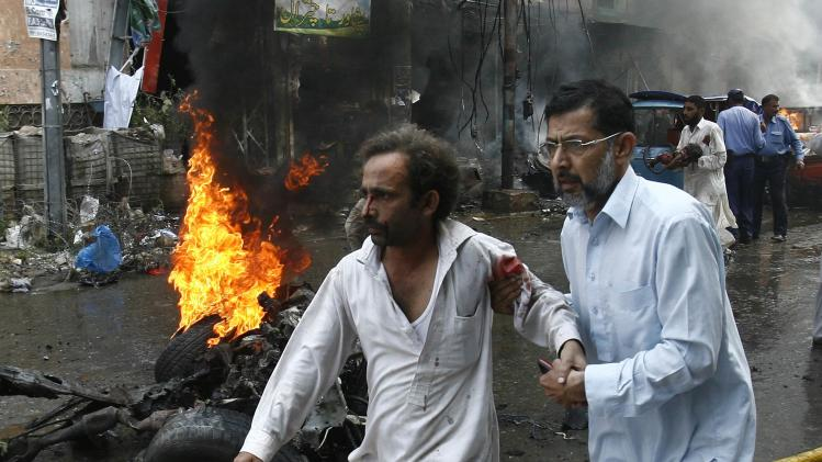 Man helps injured man walk away from the site of a bomb attack in Peshawar