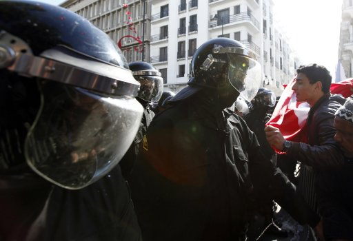 Tunisian protesters shout slogans as they clash with riot police during demonstration after death of Tunisian opposition leader Belaid, outside Interior ministry in Tunis
