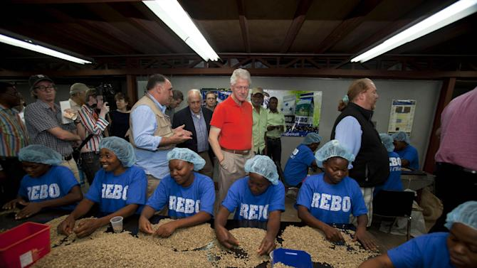 Former U.S. President and UN special envoy to Haiti, Bill Clinton watches workers sort coffee beans during a visit to the coffee production and export company Rebo S.A. in Port-au-Prince, Haiti. Monday March. 11, 2013. (AP Photo/Dieu Nalio Chery)