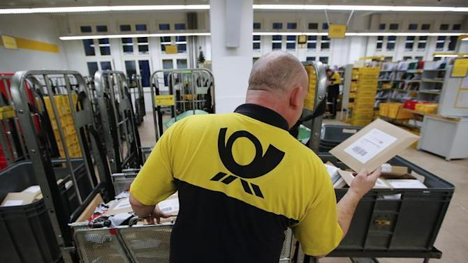 A postman of Deutsche Post sorts mail at a sorting office in Berlin