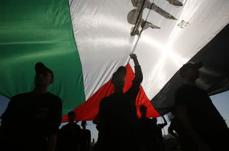Palestinian youths stand under a large Palestinian flag during a military-style graduation ceremony after being trained at one of the Hamas-run Liberation Camps, in Gaza City