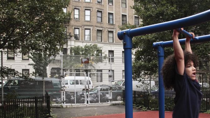 Nicholas Gayles, 6, a student at P.S. 75, plays in the school's playground  across the street from a shelter on 95th Street on Wednesday, Oct. 3, 2012 in New York.  Neighborhood residents are in turmoil, saying they were blindsided by the suddenness of the shelter's opening, sharing the same block as the school.   (AP Photo/Bebeto Matthews)