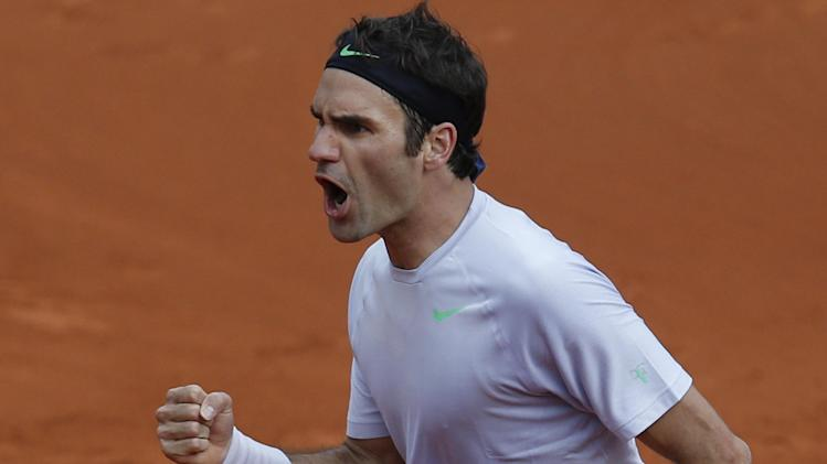 Switzerland's Roger Federer clenches his fist after scoring against France's Gilles Simon in their fourth round match at the French Open tennis tournament, at Roland Garros stadium in Paris, Sunday June 2, 2013. (AP Photo/Christophe Ena)