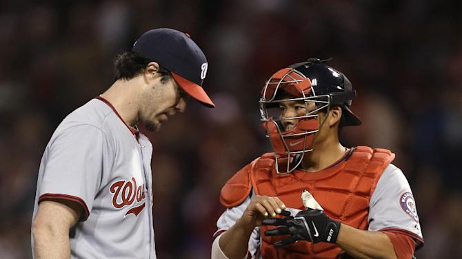 Washington Nationals starting pitcher Dan Haren stands on the mound with catcher Kurt Suzuki in the fourth inning of a baseball game against the Cincinnati Reds, Friday, April 5, 2013, in Cincinnati. (AP Photo/Al Behrman)