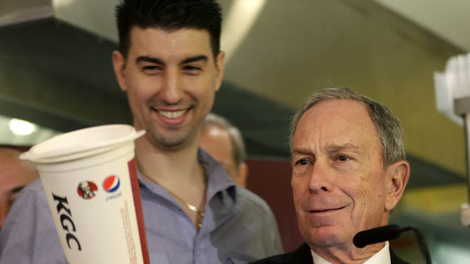 "FILE - In this March 12, 2013 file photo, New York City Mayor Michael Bloomberg looks at a 64-ounce cup, as Lucky's Cafe owner Greg Anagnostopoulos, left, stands behind him, during a news conference at the cafe in New York. The mayors of New York, Los Angeles, Chicago and 15 other cities are reviving a push against letting government food vouchers be used to buy soda and other sugary drinks. In a letter to congressional leaders Tuesday, the mayors say it's ""time to test and evaluate approaches limiting"" the use of the subsidies' for sugar-laden beverages. (AP Photo/Seth Wenig, File)"