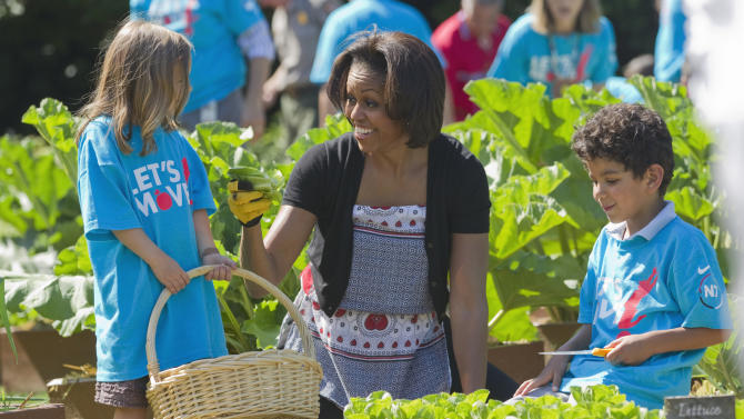 "FILE - In this June 3, 2011, file photo, first lady Michelle Obama tends the White House garden in Washington, with a group of children as part of the ""Let's Move!"" campaign. Michelle Obama has a new look, both in person and online, and with the president's re-election, she has four more years as first lady, too. The first lady is trying to figure out what comes next for this self-described ""mom in chief"" who also is a champion of healthier eating, an advocate for military families, a fitness buff and the best-selling author of a book about her White House garden. For certain, she'll press ahead with her well-publicized efforts to reduce childhood obesity and rally the country around its service members. (AP Photo/Evan Vucci, File)"