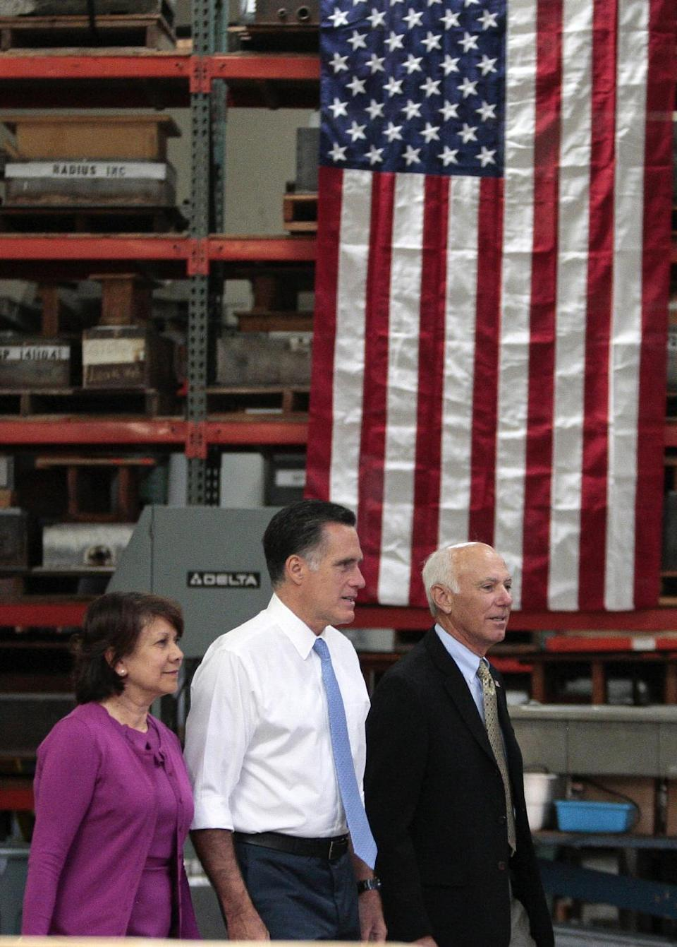 Republican presidential candidate, former Massachusetts Gov. Mitt Romney, center, arrives with Beverly Oncology and Imaging CEO Ruth Lopez Novodor, left, and Edural CEO Jim Burra for a small-business roundtable during a campaign stop at Endural LLC in Costa Mesa, Calif., Monday, July 23, 2012. (AP Photo/Jason Redmond)
