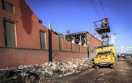Workers repair a power line near the wall of a local zinc plant that was damaged by a shockwave from a meteor in the Urals city of Chelyabinsk, on February 15, 2013