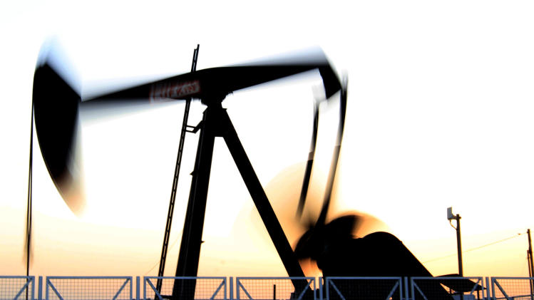An oil pump works in the Sakhir, Bahrain, desert oil fields at sunset Tuesday, July 3, 2012. The price of oil jumped more than 4 percent Tuesday to the highest level since May on renewed fears of a military conflict with Iran. (AP Photo/Hasan Jamali)