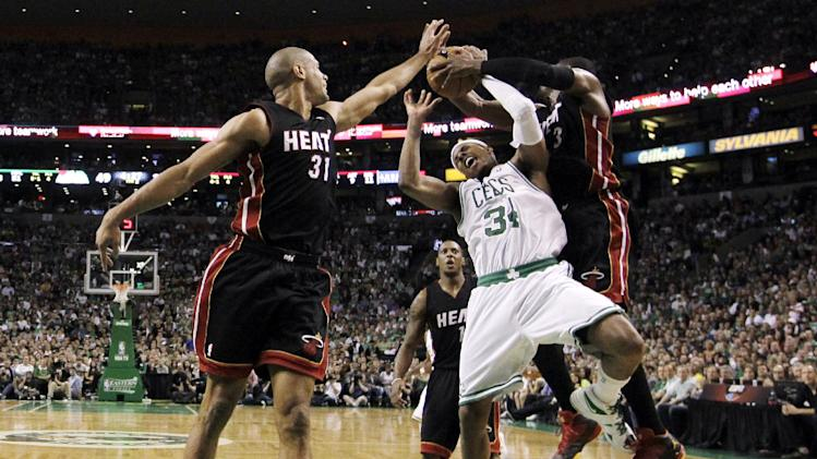 Miami Heat guard Dwyane Wade, right, ties up Boston Celtics forward Paul Pierce (34) with help from Heat forward Shane Battier (31) during the first quarter of Game 4 in their NBA basketball Eastern Conference finals playoff series in Boston, Sunday, June 3, 2012. (AP Photo/Elise Amendola)