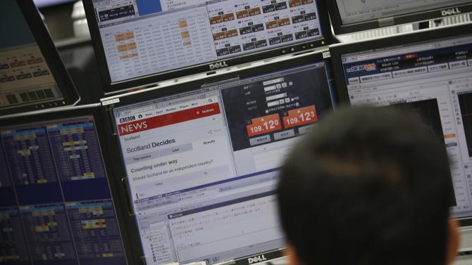 Employee of a foreign exchange trading company looks at a monitor displaying the Scottish independence vote news in Tokyo