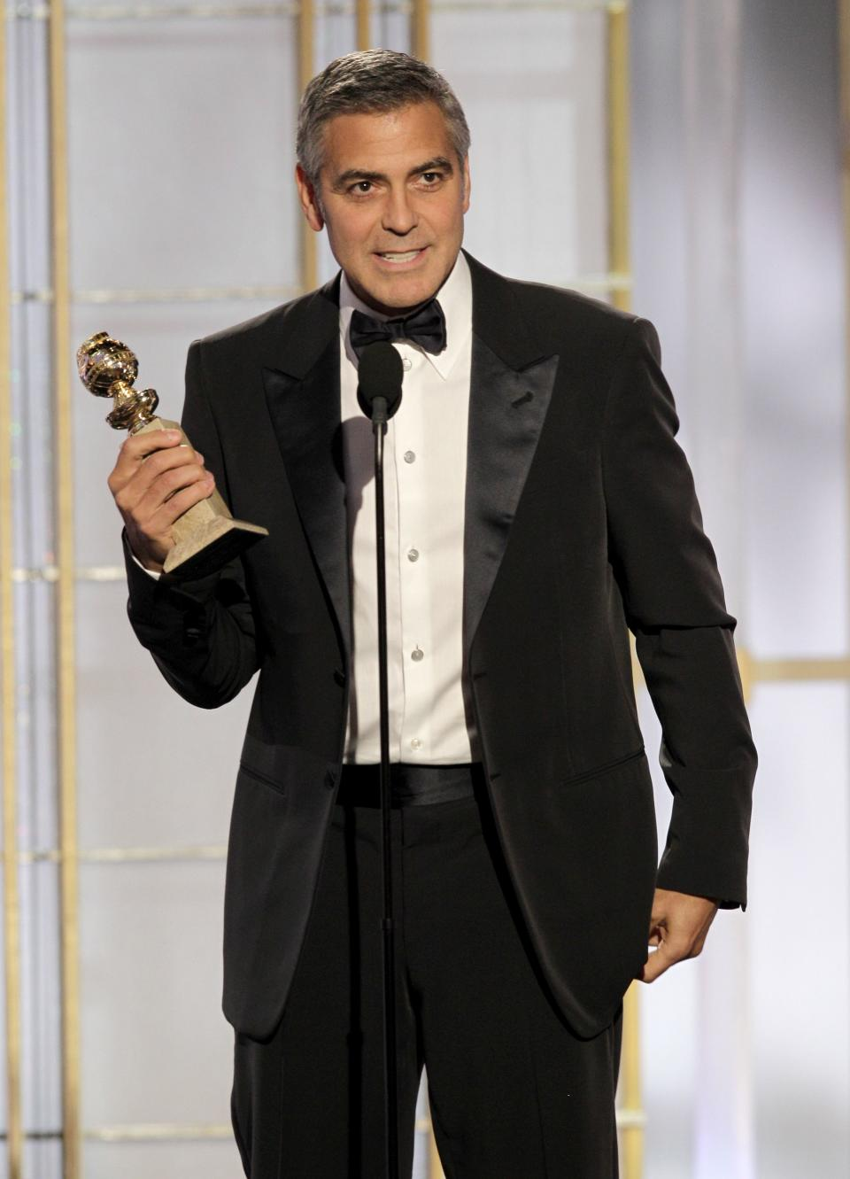 "In this image released by NBC, George Clooney accepts the award for best actor for his role in ""The Descendants"" during the 69th Annual Golden Globe Awards on Sunday, Jan. 15, 2012 in Los Angeles. (AP Photo/NBC, Paul Drinkwater)"