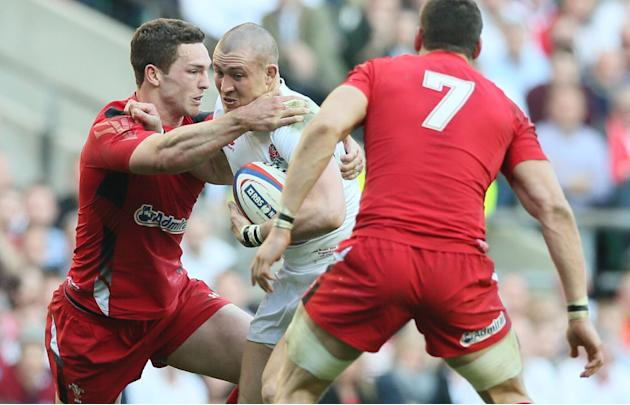 England's Mike Brown, center, is tackled by Wales' George North during the Six Nations Rugby Union match between England and Wales at Twickenham stadium in London Sunday March 9, 2014