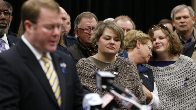 Stauffer Presser, center, reacts on Sunday, Dec. 29, 2013, as FBI Special Agent in Charge Danile McMullen announces they believe the bank robber who killed her husband, Sgt. Gale Stuaffer on Monday, was killed attempting another bank robbery in Phoniex, Ariz., on Saturday in Tupelo, Miss. (AP Photo/Northeast Mississippi Daily Journal, Thomas Wells) MANDATORY CREDIT